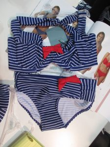 "And you know I can't resist a nautical. The Britt Stripe is available in a bandeau bikini (up to G cup), halter bikini (shown here, up to H cup), and halter tankini (also up to H cup). It offers two bottom styles; the one shown here is the ""gather pant,"" and that little red bow is removable (or you can move it to another spot on the same bikini). Too cute!"